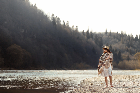 beautiful woman hipster walking on river beach in mountains,wearing hat and poncho, boho travel concept, space for text Stock Photo