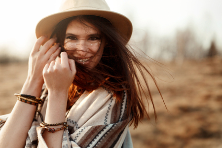 joyfull: beautiful boho woman hipster, smiling, wearing hat and poncho at sunset in mountains, true emotions, space for text