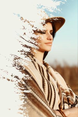 美しい自由奔放に生きる女性の夕暮れ時、山帽子とポンチョを身に着けている創造的な二重露光 写真素材