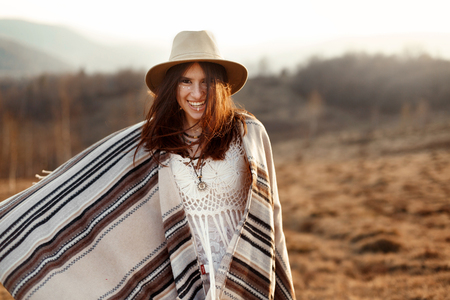 joyfull: beautiful boho woman hipster, smiling and having fun at sunset in mountains, wearing hat and poncho