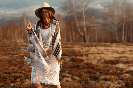 joyfull: beautiful boho woman hipster having fun, wearing hat and poncho at sunset in mountains, true emotions, space for text Stock Photo
