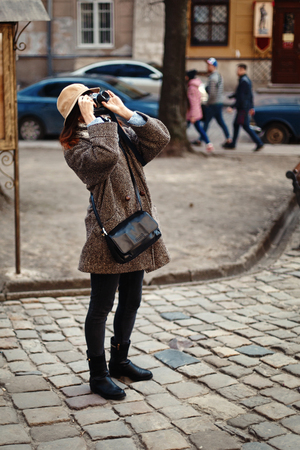 happy and stylish hipster woman taking photo with film photo camera on background of old building in european city Stock Photo