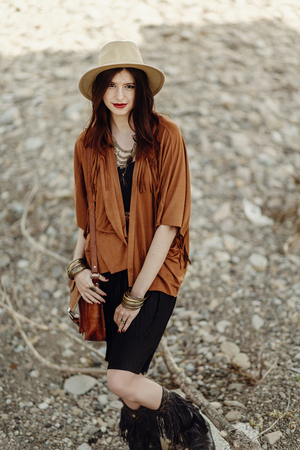 beautiful stylish boho woman hipster with hat, leather bag, fringe poncho and boots. girl in gypsy hippie look young traveler posing near river rocks in mountains. sensual look. atmospheric moment