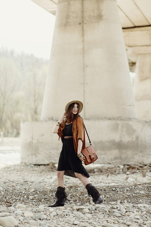 beautiful stylish hipster woman walking with hat, leather bag, fringe poncho and boots. boho traveler girl in gypsy look, near beach under bridge. summer travel. space for text. Stock Photo