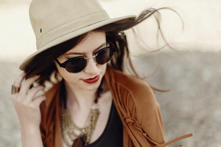 風の髪と帽子を保持しているサングラスのスタイリッシュな自由奔放に生きる女性。ジプシーで内気な少女は、山の河原近く若い旅行者を見てくだ