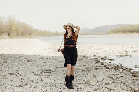 stylish boho traveler woman in hat, fringe poncho walking near water river beach in mountains, gypsy hipster girl. wanderlust summer travel. atmospheric moment. space for text. Stock Photo