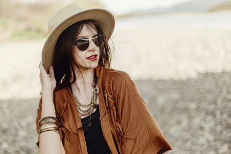 stylish boho woman in sunglasses holding hat, with windy hair. hipster girl in gypsy look, young traveler near river beach in mountains. atmospheric moment. summer travel. space for text.