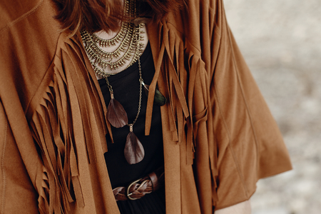 stylish boho woman look. gypsy hipster girl in fringe jacket with feather bronze accessory. wanderlust summer travel. atmospheric moment. space for text. Stock Photo
