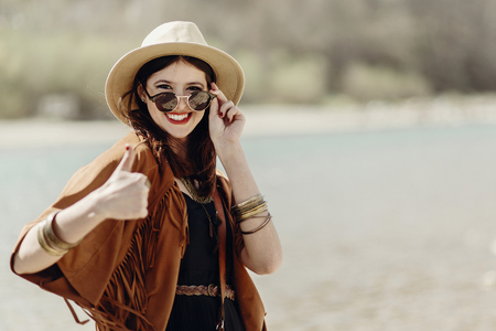 stylish traveler hipster woman smiling showing thumb up, in sunglasses with hat, leather bag, fringe poncho and accessory. happy boho girl look, wanderlust summer travel. space for text.