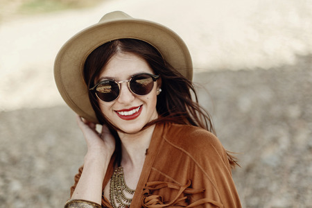 stylish boho woman smiling in sunglasses holding hat, with windy hair. hipster girl in gypsy look, young traveler near river beach in mountains. atmospheric moment.  space for text.