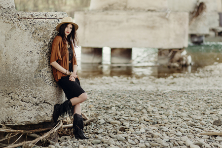 stylish boho woman with jewelry posing at river. beautiful gypsy dressed girl with hat and fringe poncho with sensual look. young girl traveler. fashionable hippie outfit. space for text