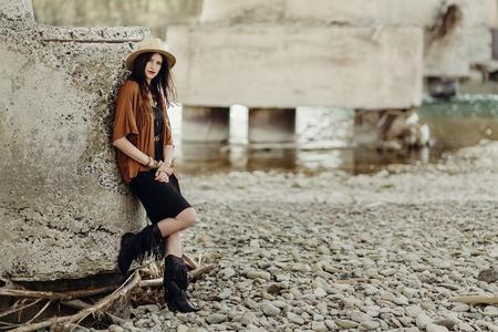 Stilvolle Boho-Frau mit Schmuck posiert am Fluss. Schöne Zigeuner gekleidet Mädchen mit Hut und Fransen Poncho mit sinnlichen Blick. Junger mädchenreisender Modisches Hippie-Outfit. Platz für Text Standard-Bild - 75056533