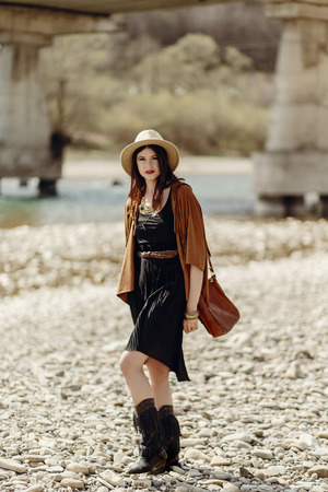 stylish boho gypsy woman in hat, fringe poncho and boots walking on river beach. hipster traveler girl look, summer travel. atmospheric moment. space for text.