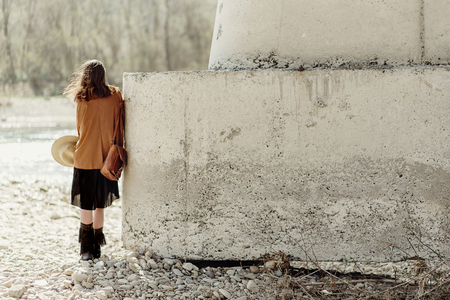 stylish boho woman posing at river under stone bridge, back view. beautiful gypsy girl with hat and fringe poncho and boots. young girl traveler. atmospheric moment. space for text Stock Photo