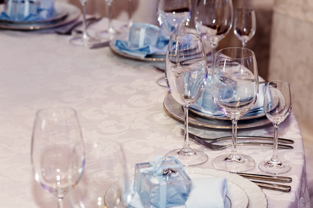 luxury wedding arrangement of stylish glasses plates on napkins and silver cutlery on round table at wedding reception. expensive catering. space for text . decor for feast at holidays