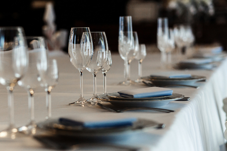 wedding feast: luxury wedding reception. stylish glasses, plates on napkins and silver cutlery and gifts for guest on round table at expensive catering. space for text. decor for feast at holidays