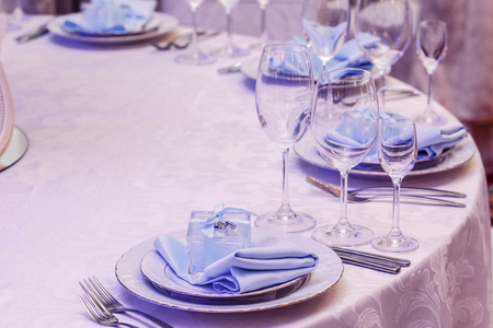 formal dinner party: luxury wedding arrangement of stylish glasses plates on napkins and silver cutlery on round table at wedding reception. expensive catering. space for text . decor for feast at holidays