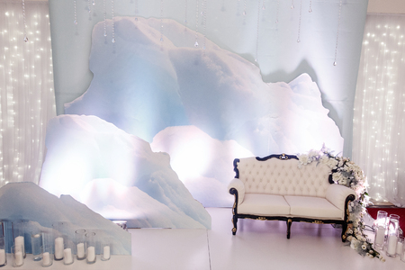 luxury wedding decor for photo booth zone. stylish chair sofa with flowers and candles at winter snow installation. arrangements of decorations at wedding reception. expensive. space for text. Stock Photo