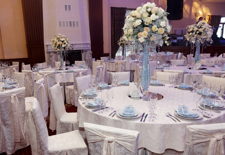 luxury decorated tables at rich wedding reception. stylish arrangements of flowers and jewels on table in glass vase, dish and glasses on tablecloth. expensive catering. space for text Stock Photo
