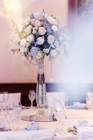 luxury wedding decor with flowers and glass vases with jewels on round tables. arrangements of decorations at wedding reception. expensive catering. space for text
