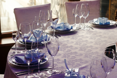 luxury wedding reception. stylish glasses, plates on napkins and silver cutlery and gifts for guest on round table at expensive catering. space for text. decor for feast at holidays