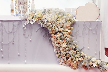 luxury decorated table flowers of hydrangea and roses at rich wedding reception. golden stylish arrangements at centerpiece for bride and groom, expensive catering. space for text