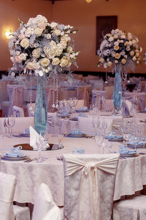 luxury wedding decor with flowers and glass vases and number of setting on round tables. arrangements of decorations at wedding reception. expensive catering. space for text Stock Photo