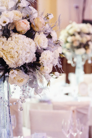 royal wedding: luxury wedding decor with flowers of roses and hydrangea closeup in glass vases with jewels. arrangements decorations at wedding reception. expensive catering. space for text Stock Photo