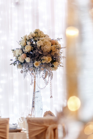 luxury wedding decor with flowers and glass vases and number  of setting on round tables. arrangements of decorations with stones jewels at wedding reception. expensive catering. space for text
