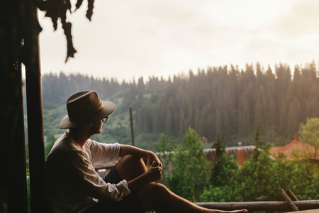 hipster man sitting on porch of wooden house  looking at woods in evening, calm moment, summer vacation concept, space for text