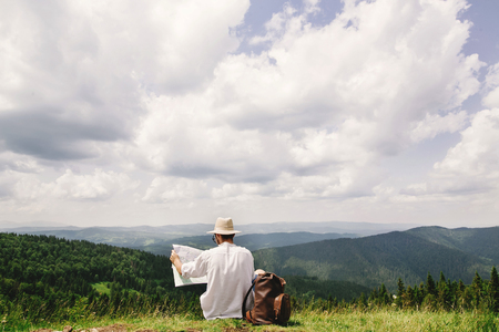 stylish hipster traveler man with backpack sitting at top of mountains with amazing view and holding map and exploring , summer travel concept, space for text