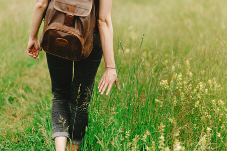 세련 된 힙 스터 여자 잔디에서 걷고 손을 잡고 여름 산에서 야생화, 여행 개념, 평화로운 휴식 순간 스톡 콘텐츠