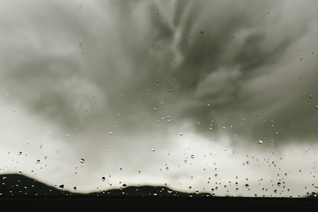 raindrops on window glass on background of gray clouds, rainy weather in mountains, space for text