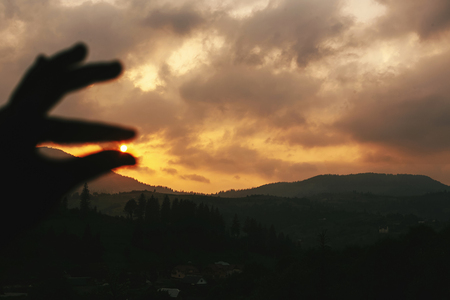 silhouette of hand catching sun in sunset in mountains landscape, tranquil moment of relax concept, space for text Stok Fotoğraf