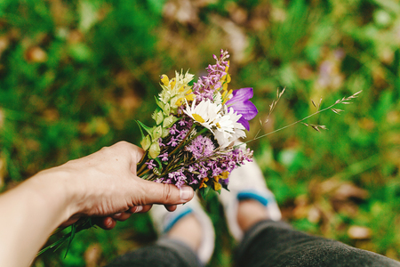 stylish hipster woman with backpack gathering and holding  wildflowers in hand, view at legs in sneakers, in summer mountains, travel concept, space for text Stock Photo