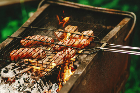 delicious grilled sausages roasting on grates with flames and smoke, bbq outdoors at summer picnic, camping concept