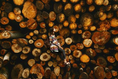 Elegante donna hipster con zaino seduto al mucchio di legna da ardere, relax e pensare, momento atmosferico, scala umana, spazio per il testo