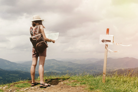 stylish hipster woman traveler with backpack holding map and exploring on top of mountains, travel  concept, space for text Stock Photo