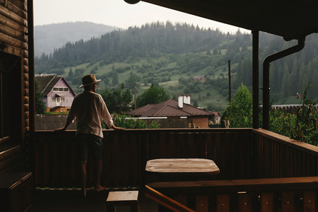 hipster man standing on porch of wooden house and relaxing looking at mountains in evening, calm moment, summer vacation concept, space for text