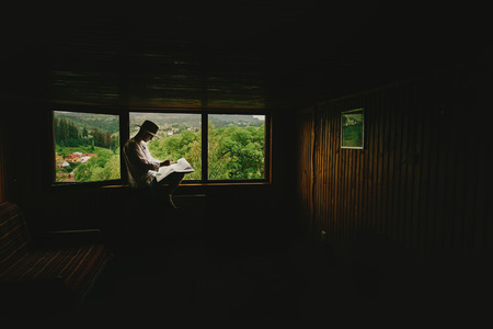 architect drawing: stylish hipster man sitting at window with view on mountains and holding map and exploring in wooden house, summer travel concept, space for text