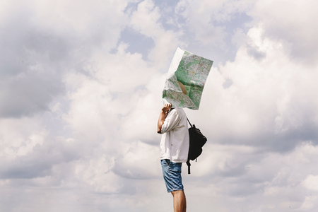 hipster traveler on top of mountains with amazing sky clouds view and map at his head, funny moment,  travel adventure and gps concept, space for text Stock Photo