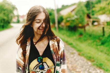 スタイリッシュな流行に敏感な女性の笑顔と落ち着いた気分で日当たりの良い夏の山の道旅行のコンセプト