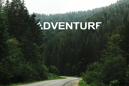 adventure sign word, beautiful view of road among trees in forest light, moody atmospheric moment, wanderlust concept, space for text Stock Photo