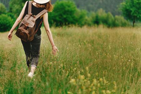 草の中を歩いてスタイリッシュな流行に敏感な女性と夏の山のハーブ野草を手で押し、旅行の概念、穏やかなリラックスの瞬間