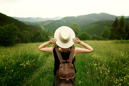 woman traveler with backpack holding hat and looking at amazing mountains and forest, wanderlust travel concept, space for text, atmosperic epic moment Stockfoto