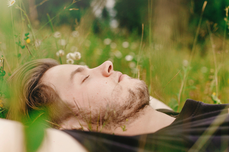 stylish hipster man  lying on sunny grass in meadow and relaxing in summer mountains, travel concept, space for text