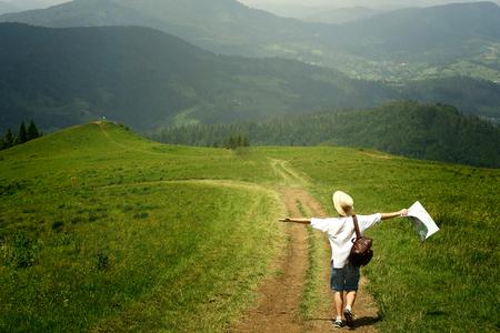 man reiziger bedrijf kaart en wandelen naar de top van zonnige heuvel op de achtergrond van verbazingwekkende bergen, zomer reizen concept, ruimte voor tekst Stockfoto