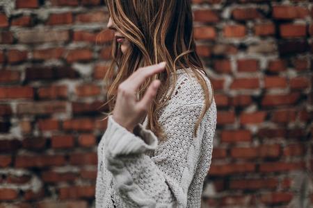 スタイリッシュな流行に敏感なジプシーの女、レンガの壁の背景にニットのセーターでポーズをとって髪を保持しています。大気中の官能的な瞬間