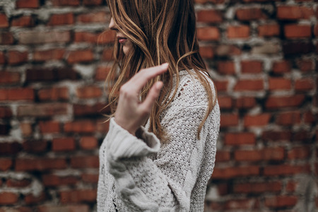 stylish hipster gypsy woman posing in knitted sweater on background of brick wall, holding hair. atmospheric sensual moment. boho country fashionable look. free people