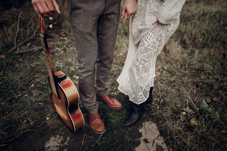 man with guitar holding hands with his boho gypsy woman closeup in windy field. atmospheric sensual moment. stylish hipster couple in fashionable look. rustic wedding concept